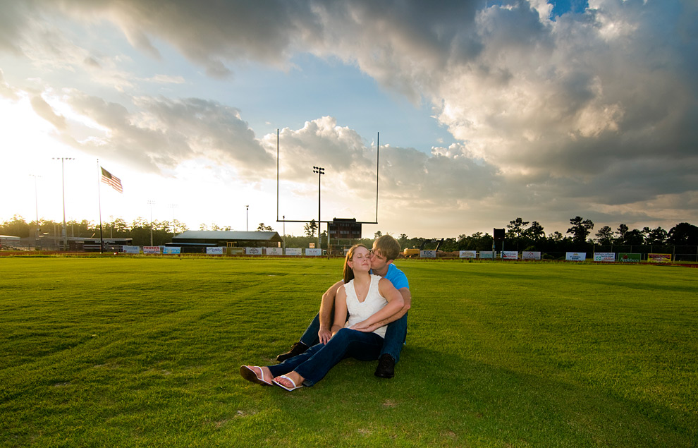 Gal sitting between guy's legs in the middle of a football field in the afternoon