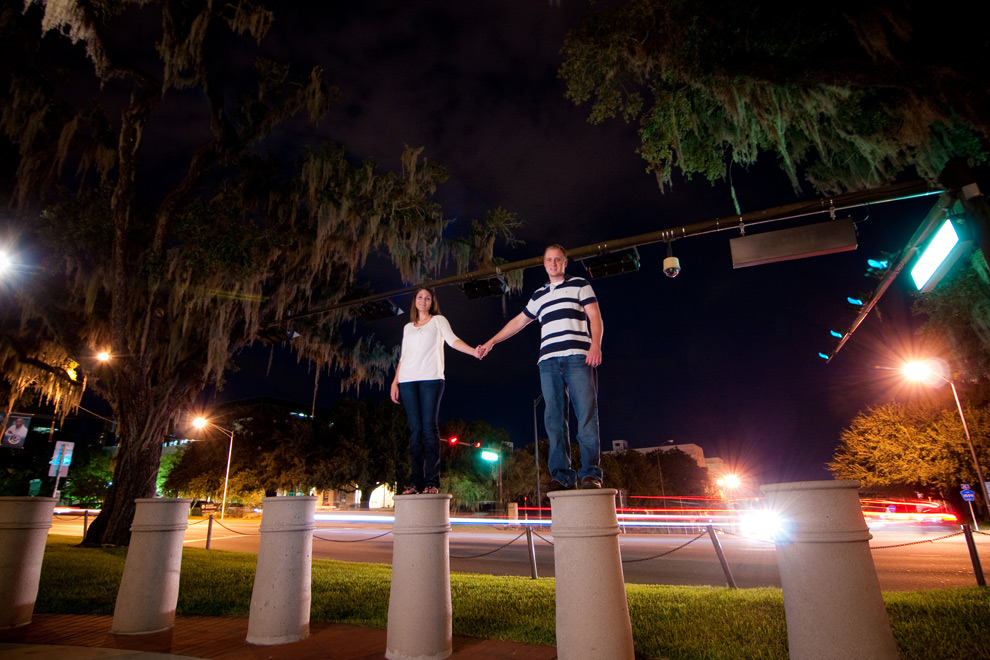 Standing in front of Monroe Street holding hands. A long exposure produces light streaks from the cars driving in the background.