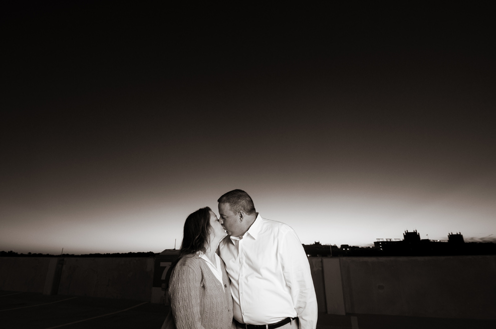 Kissing in black and white with the sunset vignette behind