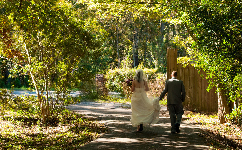 Bride and groom walking to secluded location for pictures