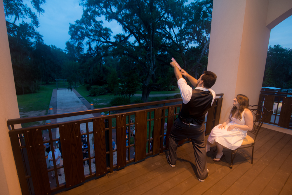 Groom in a hero pose flings the garter off a balcony to the single male guests below