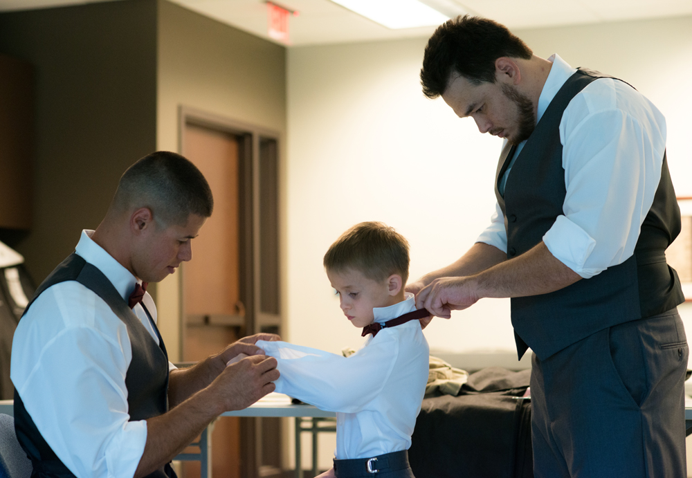 Groomsmen helping ring bearer get dressed