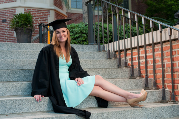 Graduating student wearing cap and gown, sitting on the steps at Wescott on FSU campus