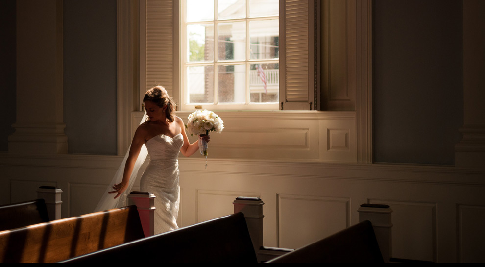 Bride walks past a large window at Trinity United Methodist Church