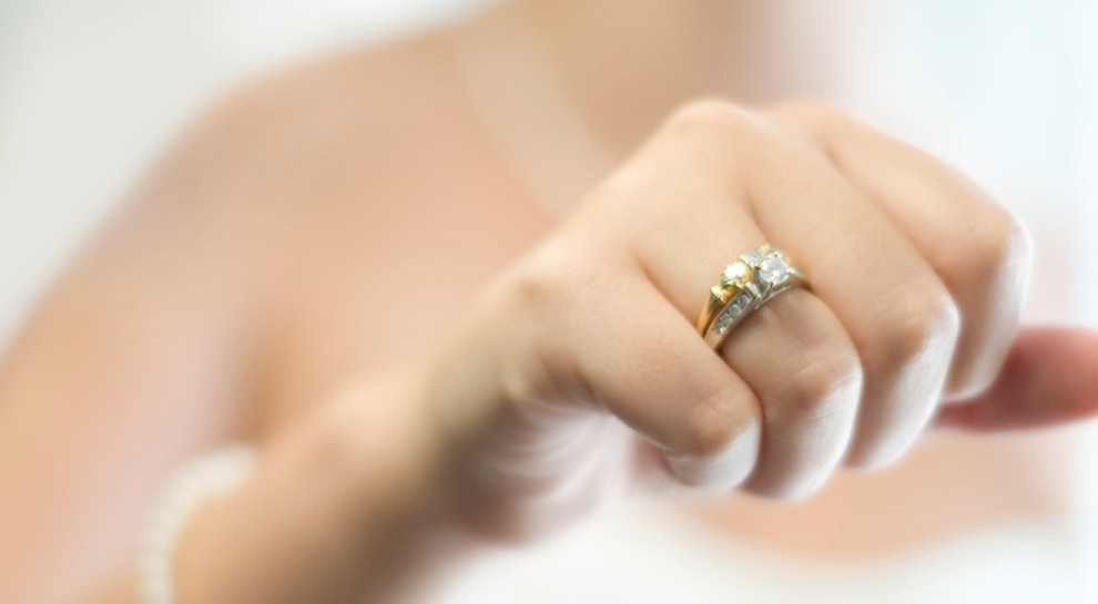Bride holding up engagement ring toward the camera