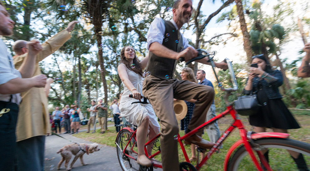 Newly wedded couple hop on a tandem bike to exit their reception