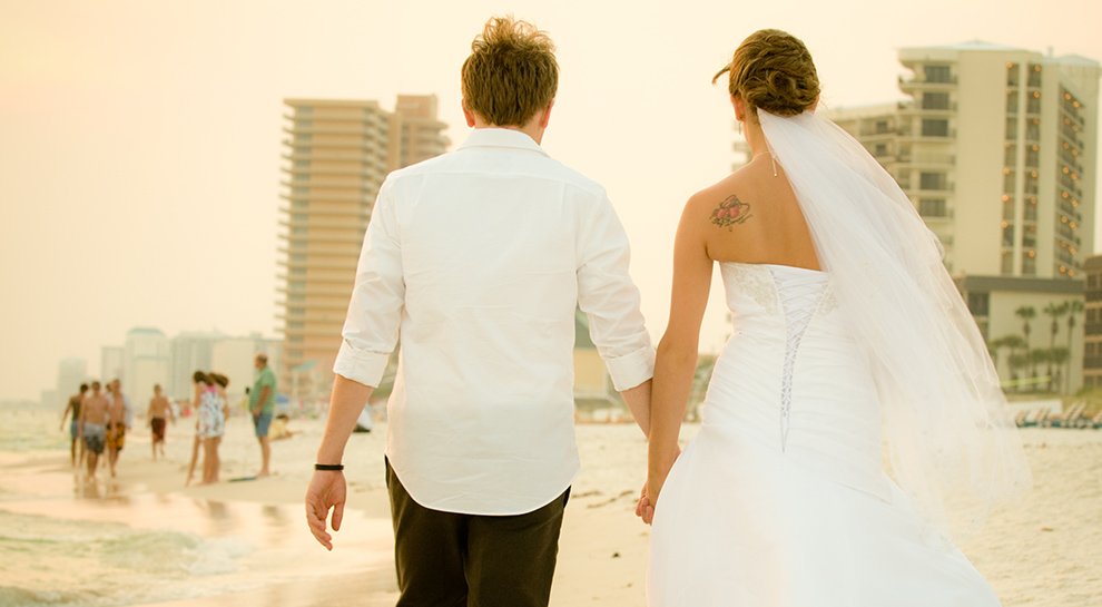 Married couple hold hands and walk down the sand of Panama City Beach