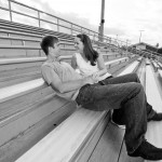 Engaged couple sits by themselves on the bleachers at their old high school