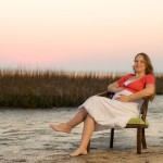 Sitting in a chair on the beach, rubbing a pregnant belly at sunset