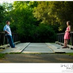 Guy and girl exchange glances as they stand on opposite sides of a bridge