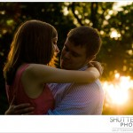 An engaged couple holding each other as the sun sets.